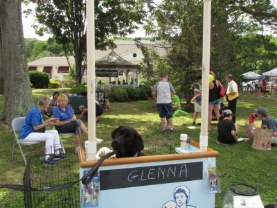 Glenna, a Guiding Eyes for the Blind Dog, mans the Puppy Kissing Booth