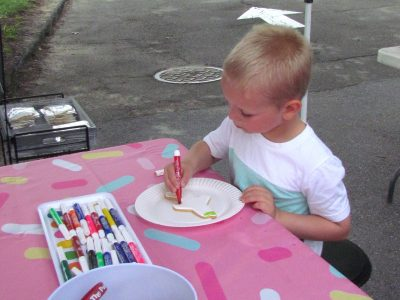 A customer trying out color-a-cookie at the Painted Cookie booth.