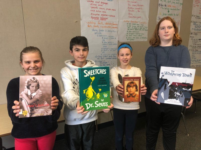 Four students holding four books