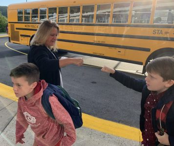 Fist bumps for returning students at Cider Mill.