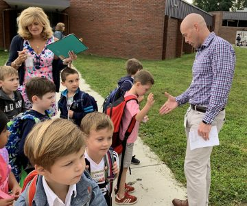 Assistant principal Jeremy Cross greets a student.