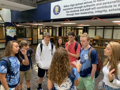 Safe school climate coordinator Kim Zemo (back to camera) speaks to a group of students on the first day back at Wilton High School.