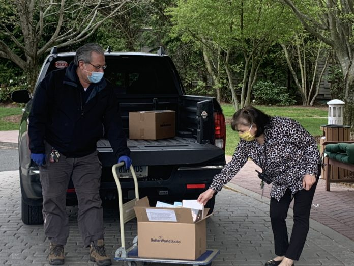 Carmela Tornatore, Director of Recreation for The Greens at Cannondale, looks over a collection of books being delivered by Rich Hubli, building operations manager for Wilton Library.